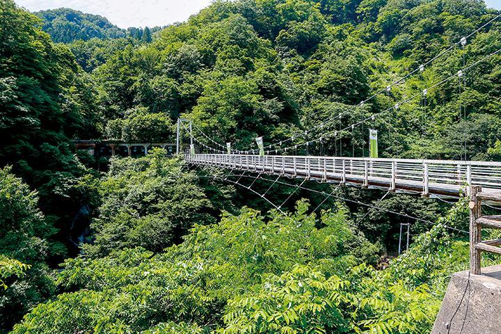 梵字川に架かる、ふれあい橋。切り立った山が、四季折々の美しい表情を見せてくれる。撮影は昨年7月